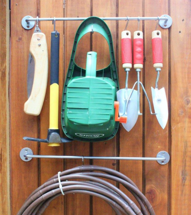 Two kitchen rods attached to the wall with hanging short-handled garden tools.