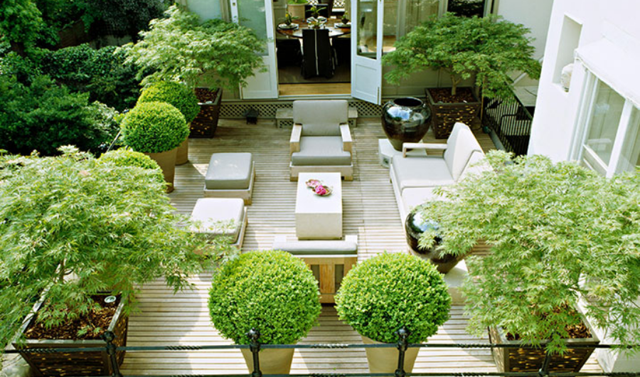 This roof garden features off white and light grey furnishings that complement well with potted topiaries and trees in the four corners of the roof space.