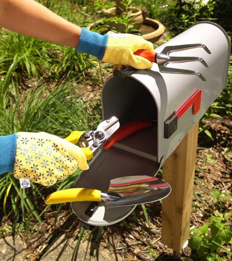Gardener wearing yellow gloves storing garden tools onto the metal mailbox.