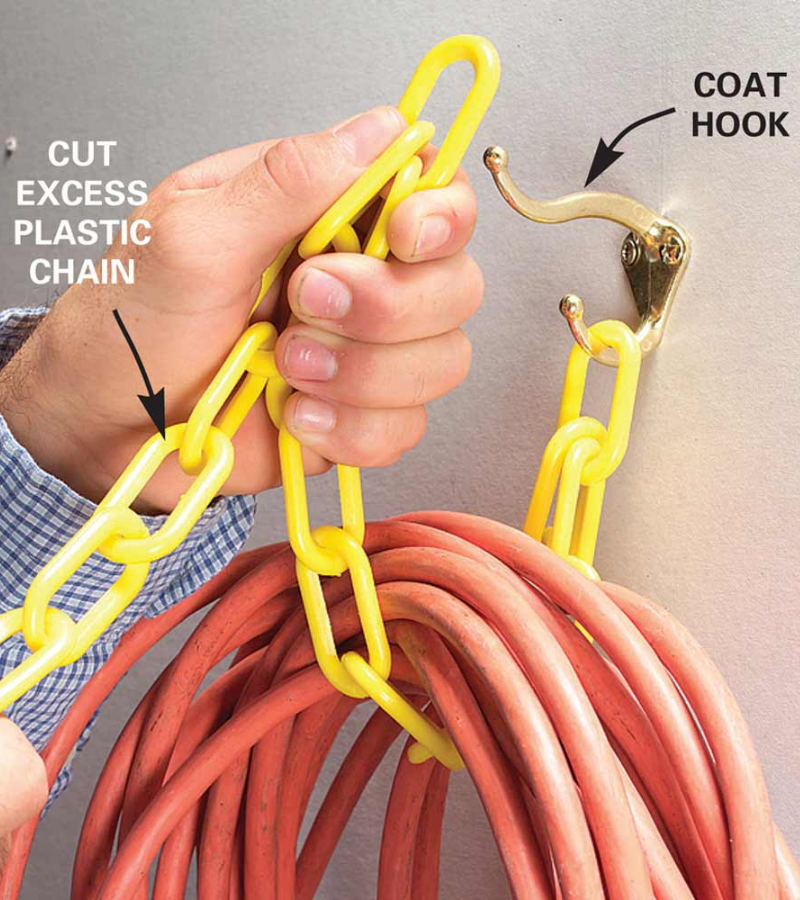 The orange garden hose hangs with a yellow plastic chain on the coat hook.