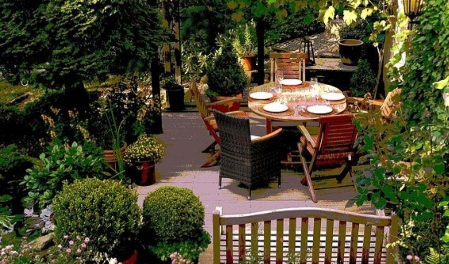 The garden features dining furniture with plates and drinking glasses on the top, wooden bench, and sideyard spaces that are full of lush vegetations.