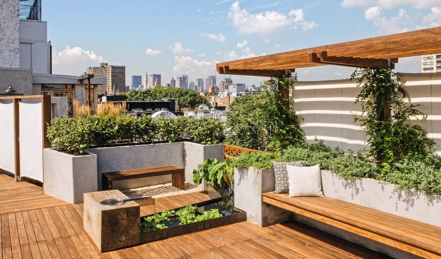 The roof garden features wooden pergola with vines, wooden raised beds filled with plants and long