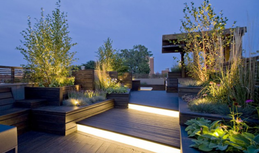 This roof garden has contemporary lighting under the two-tier wood decking and crafty lighting illuminating the trees in raised beds, accentuating the skyline backdrop.