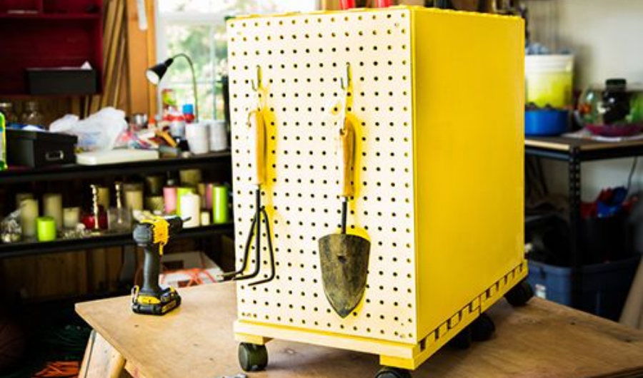 Mobile garden tool cabinet painted in yellow with pegboard sidings.