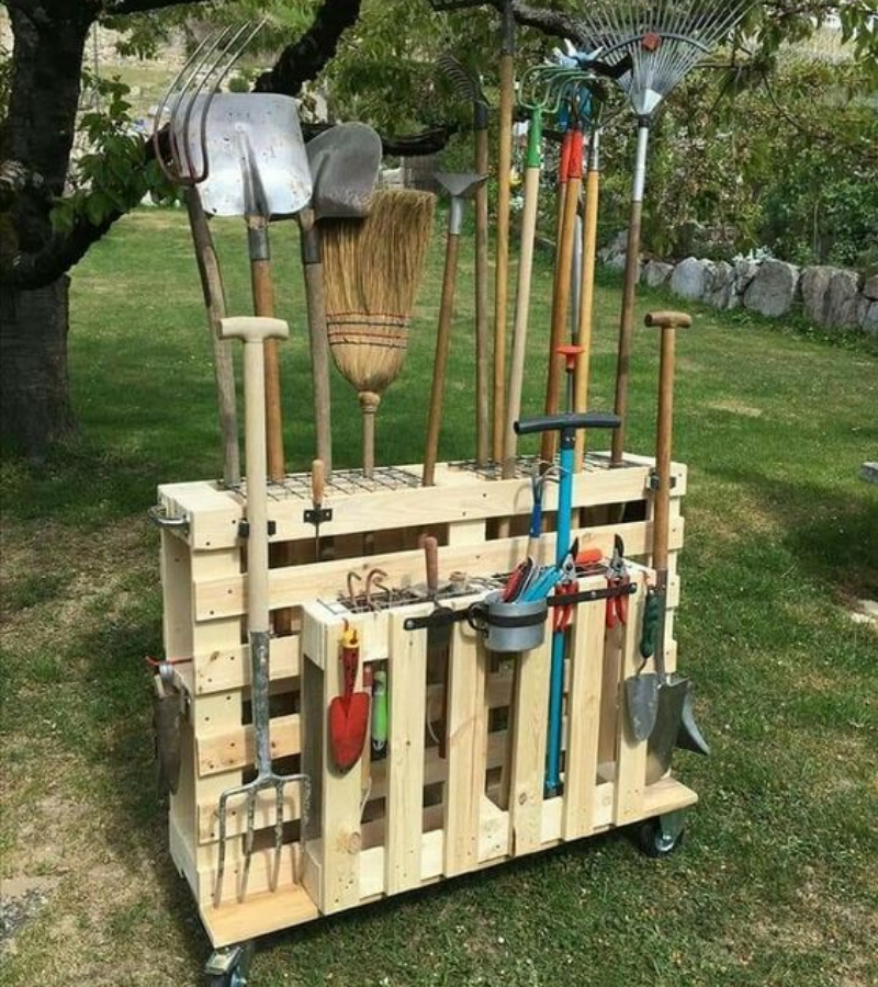 Unpainted DIY pallet garden tool trolley full of garden tools.