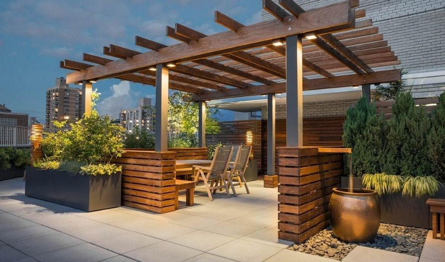 The rooftop garden has a wooden pergola with classic lightings. It has dining furniture and wooden raised beds filled with verdant plants.