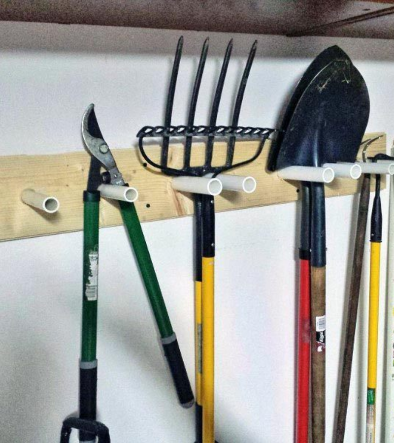 Small size PVC rack mounted on the wall with shovels, garden forks, and loppers.