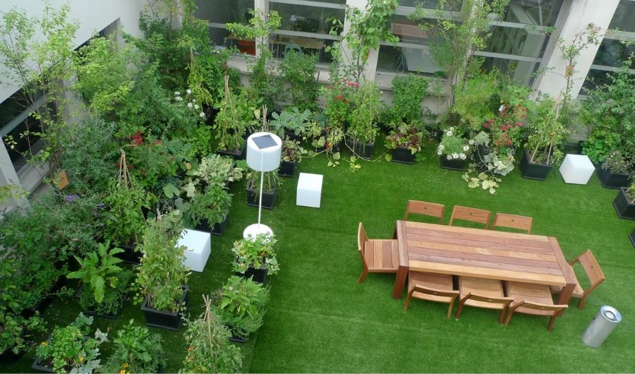 An aerial view of the roof garden with dining furniture at the center, three woodblocks and a lampstand painted in white positioned near the surrounding plants.