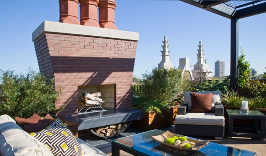 The roof garden features a well structured fireplace with logs and a couple of seatings with patterned athrow pillowsand glass table at the center.