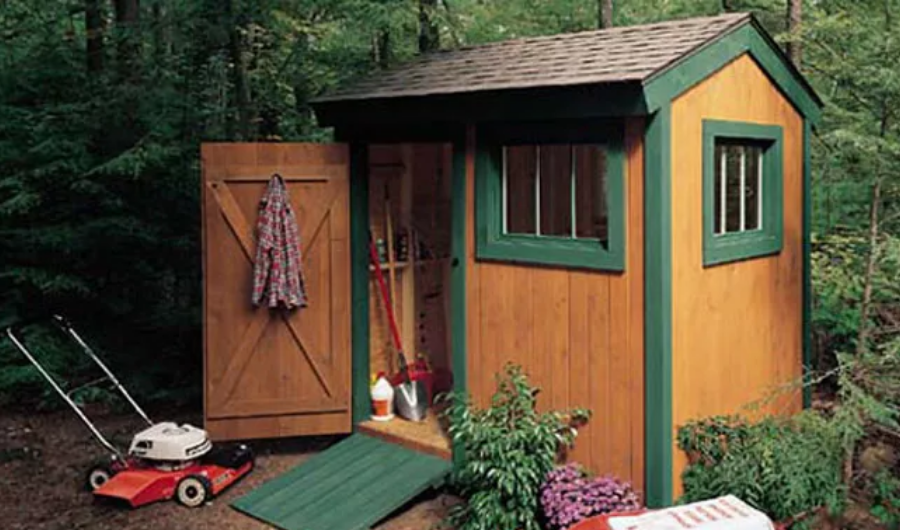 A small garden shed built out of wood with an opened door.