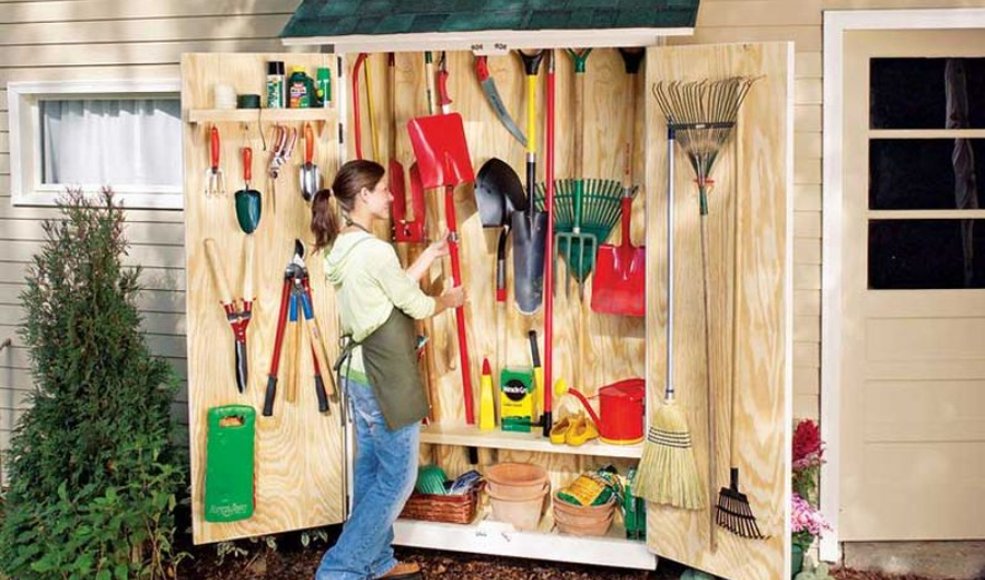 Wooden garden tool cabinet full of various gardening items.