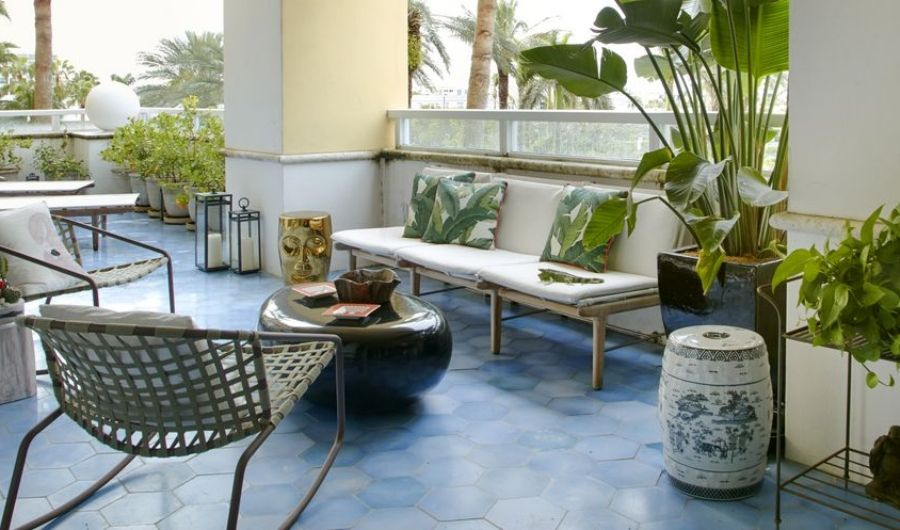 The roof garden features ocean blue tiles, tropical potted plants, simple rectangular seating with three throw pillows, and an oval ceramic center table.