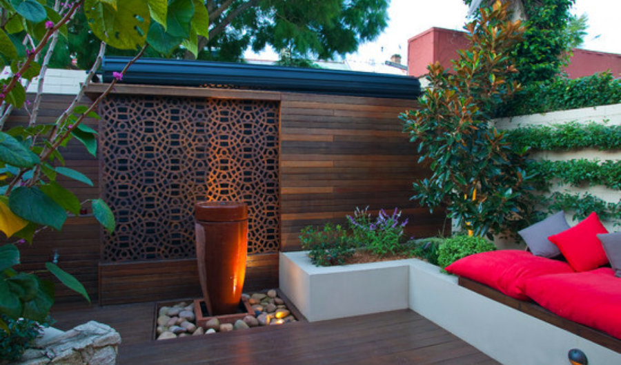 This Japanese-inspired roof garden features a tubular ceramic pot standing on the stone bed and walled garden with comfortable rectangular seating full of brown and red throw pillows.
