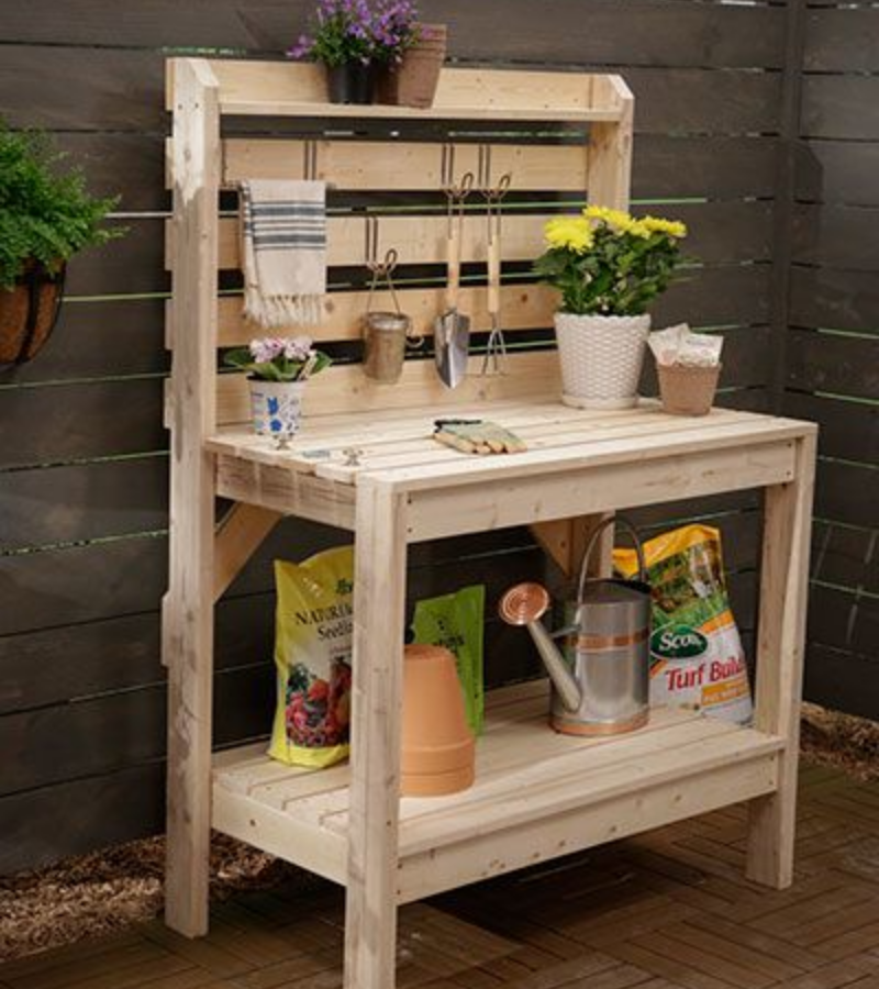 A DIY unpainted farmhouse style potting bench with a bottom shelf where the watering can, clay pots and potting soil are stored.