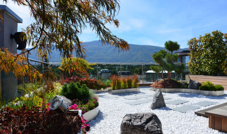 This rooftop zen garden features stone, gravels, concrete path, and surrounding plants with green mountain and blue sky that serve as the backdrop.