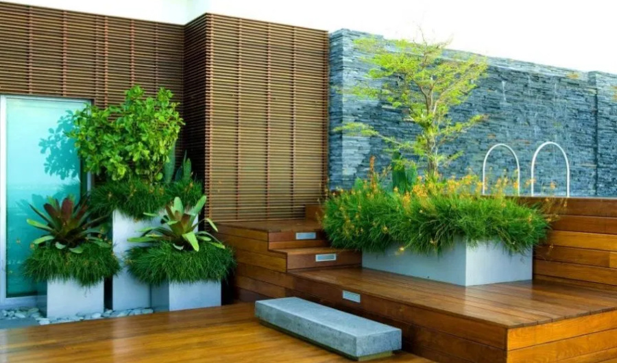 This rooftop garden displays wood decking and wooden planters filled with lush and flowering plants, accented with innovative bamboo roll backdrop.