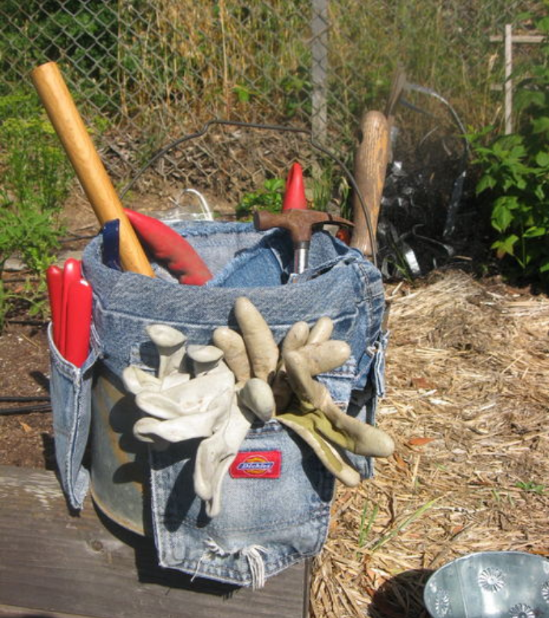 Stainless container pot with tailored pocket and jean pockets full of garden tools.