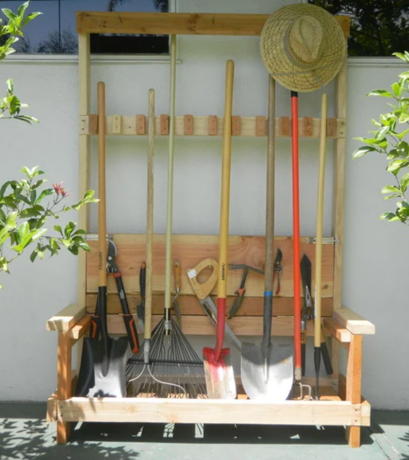 A no hook wooden garden tool rack full of garden tools and one gardener's hat.