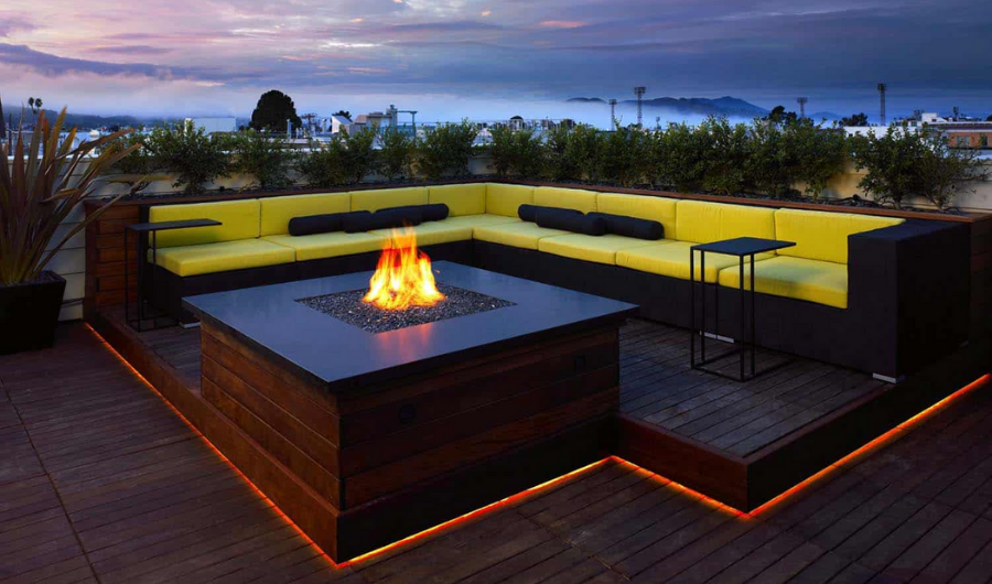 The roof garden showcases a contemporary L shaped seating with yellow cushions, shrubs, fireplace, deck border lighting, and panoramic view display undeniable luxury, particularly at night.