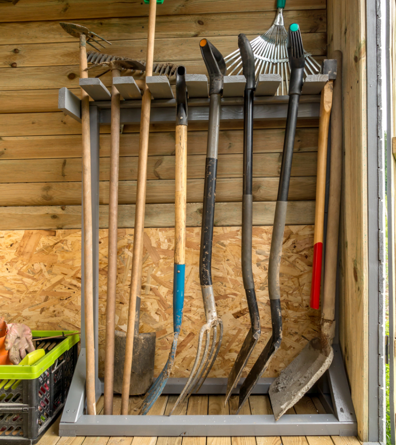 An easy DIY wooden rack in the colour grey with organized garden forks and shovels.
