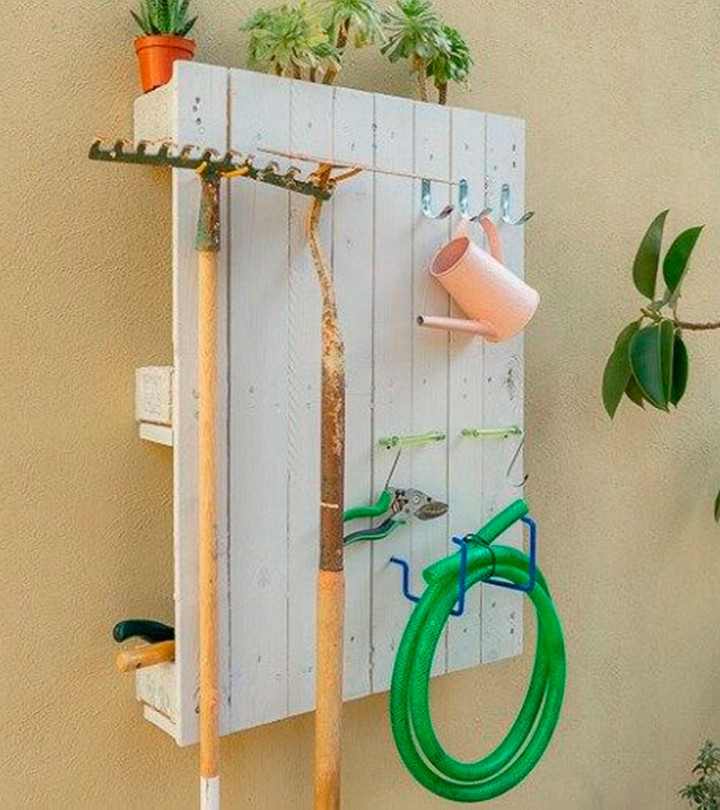 Painted in white, a pallet mounted on the wall used as a garden tool organizer.