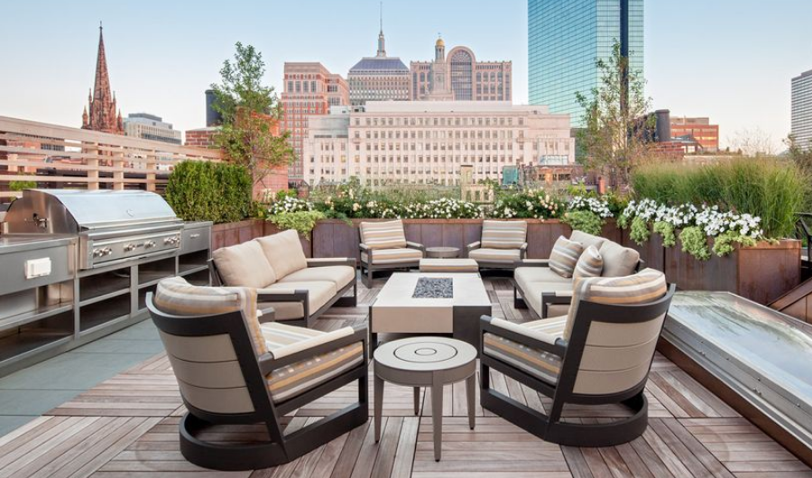 This rooftop garden features comfortable seatings with cream fabric cushions and a stainless steel BBQ grill. It has sideyard wooden raised beds filled with greens and hanging plants with white blooms.