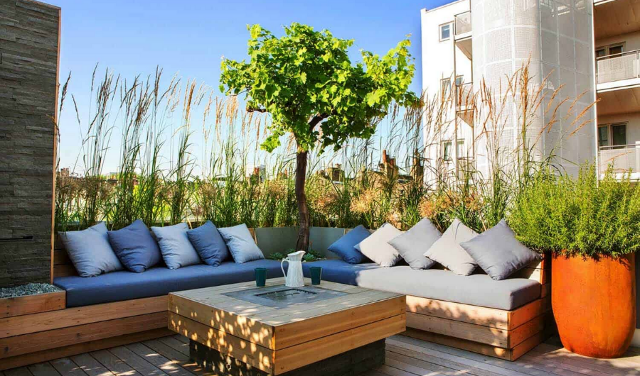 The comfortable L-shaped seating with plain grey cushions along with the tree in the corner and tall grass backdrop, terracotta potted plants and wooden center table, make the overall look of the garden dynamic and fresh.