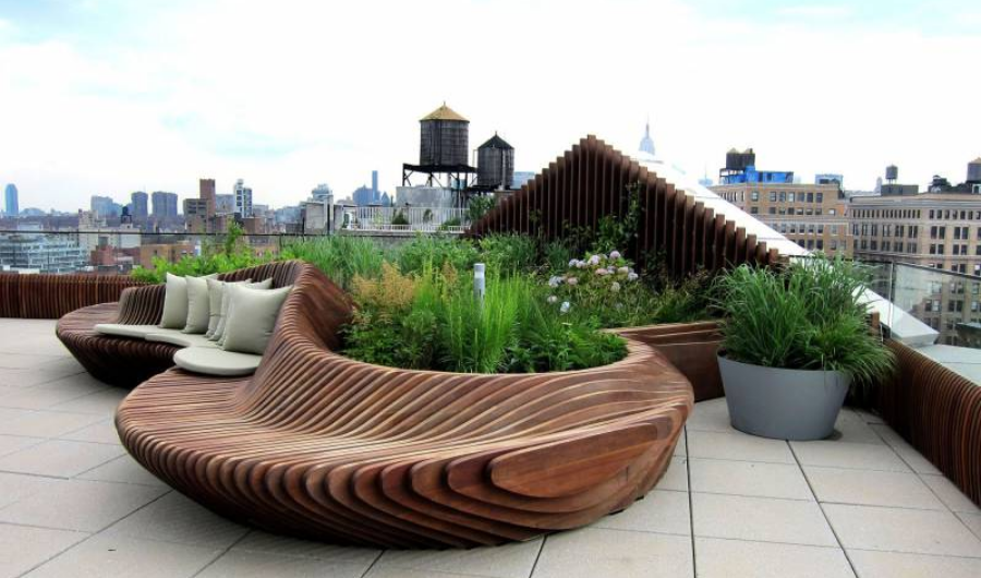 The dune-inspired innovative seating with comfortable cushion and throw pillows is the focal point of this roof garden. It has flowering plants on the circular center space and potted grass next to it.
