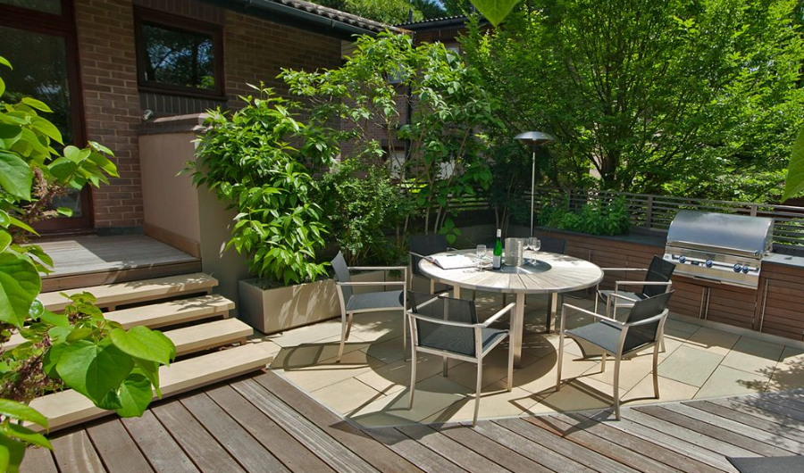 This rooftop garden features dining furniture, stainless steel BBQ grill, and angular hardwood decking.