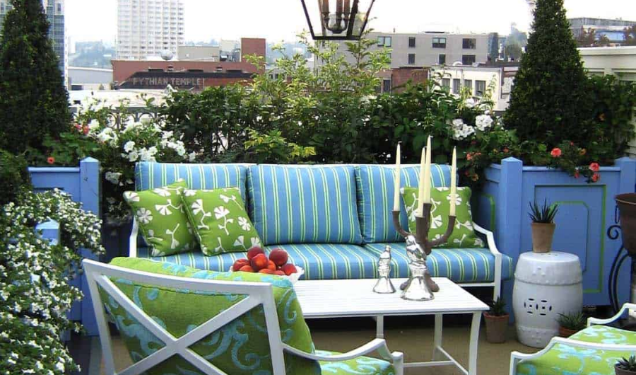 The rooftop garden features comfortable furnishing with blue-green patterned cushions, white ceramic pots, and lush vegetation backdrop