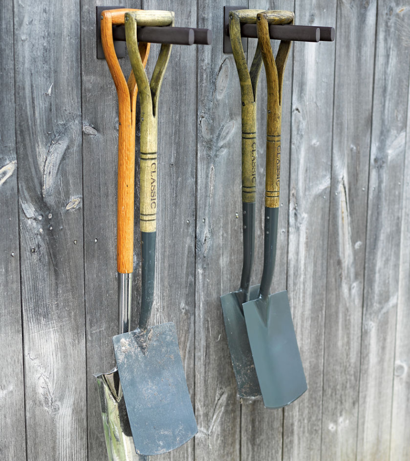 Two wooden racks mounted on the wall, each with two hanging shovels.