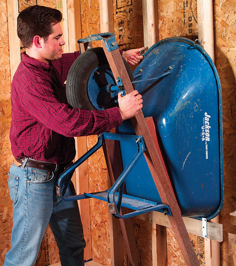 A man hangs the blue wheelbarrow up on the wall stud with hooks and metal plates as the tool organizer.