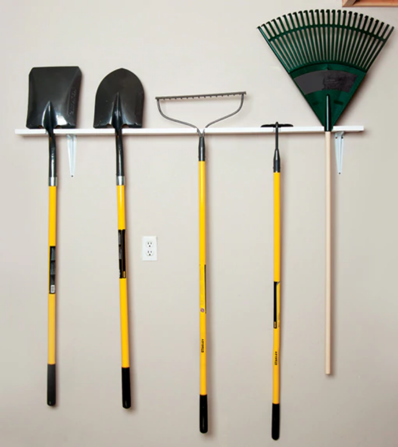Single shelve wooden garden tool rack with long-handled garden tools.
