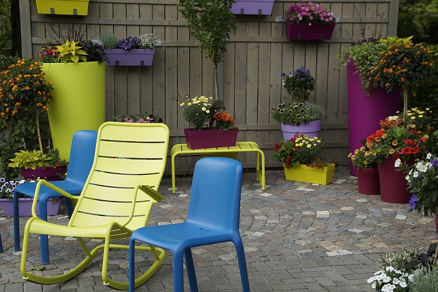 The garden features colourful potted plants and chairs with a wooden backdrop.