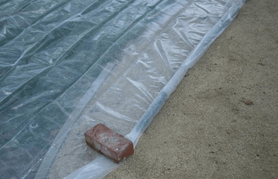 Soil covered with clear plastic-sheet secured with brick clay.