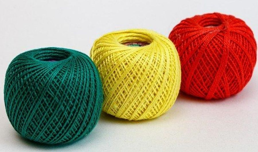 Red, yellow, and green spools of yarn.
