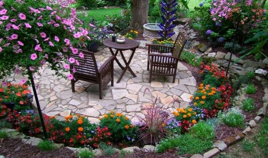 Set of tea table at the center of mosaic tiles surrounded by colorful flowering plants.