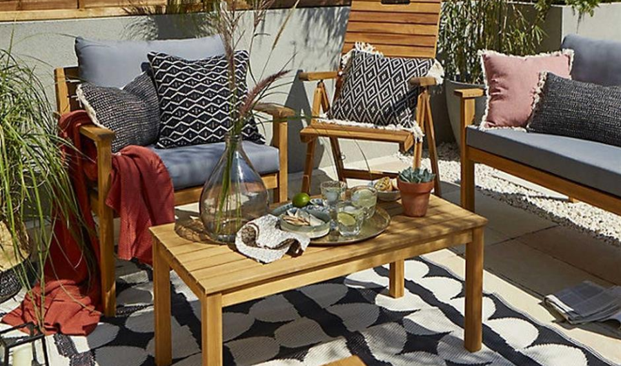 Wooden dining table with sets of throw pillows and cushions in the small and sunny deck garden.