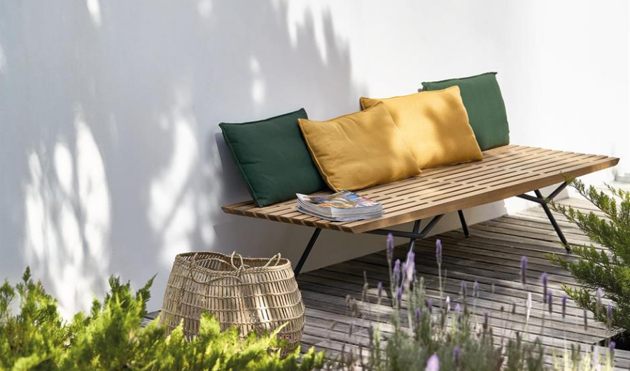 A wooden bench with magazines and four throw pillows placed in the small deck garden.