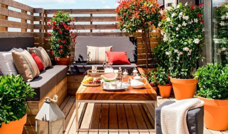 A small wooden deck full of flowering plants in planters, throw pillows and cushions, rectangular table at the center, and a wooden backdrop.