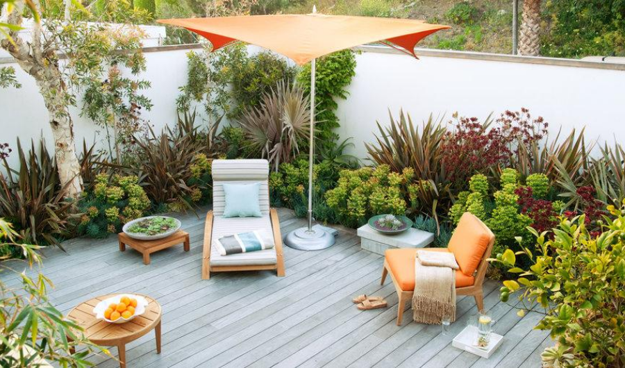 Beach setup with wooden lounger, orange umbrella stand, bright-coloured cushions, and potted plants, surrounding in the small wooden deck garden.