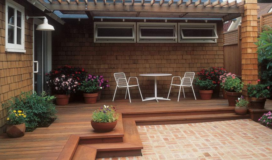 Two steps on a hard-edged wooden deck with flowering plants and a white painted iron tea table.