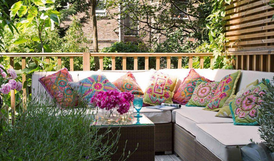 Set of rattan furniture with plain white cushions, patterned throw pillows, potted plants and wooden railings to section off a deck garden.