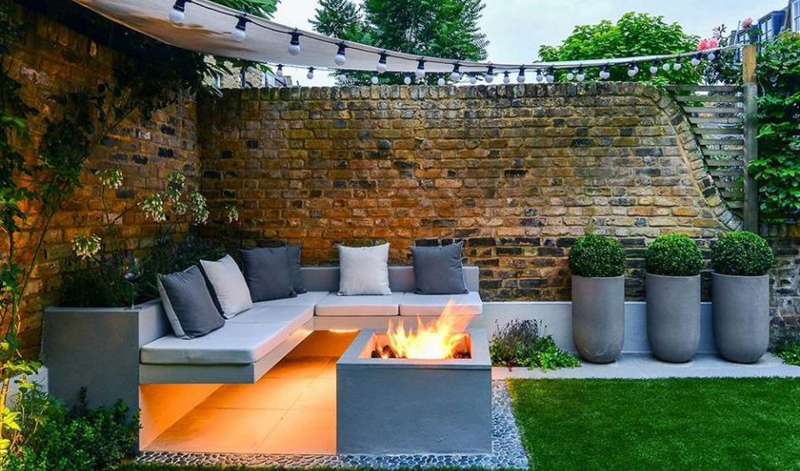 An L-shaped seating, galvanized planters, throw pillows in white and grey, and a concrete fireplace in the small deck garden.