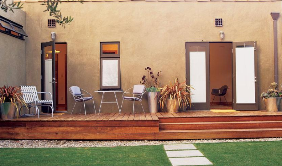 An iron coffee table and potted planters displayed on the small wooden balcony deck.
