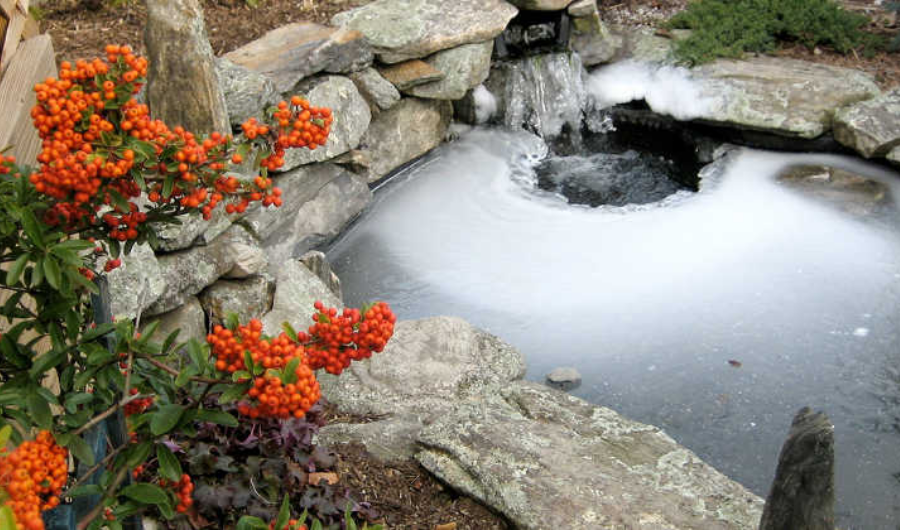 An icy pond with a waterfall and hole in it surrounded by orange flowers