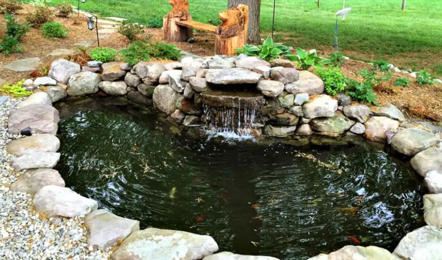Deep koi pond with egg-shaped stone edging.