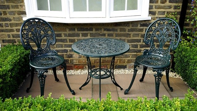 Set of outdoor iron table and two chairs surrounded with lush hedges.