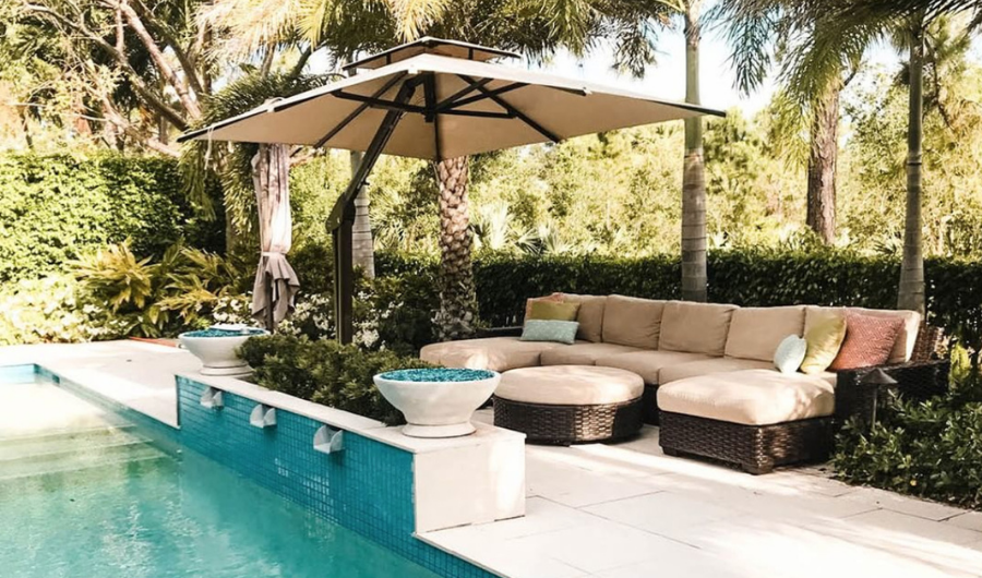 A luxurious setup of lounge chairs and a large patio umbrella complement the hedge garden and pool.