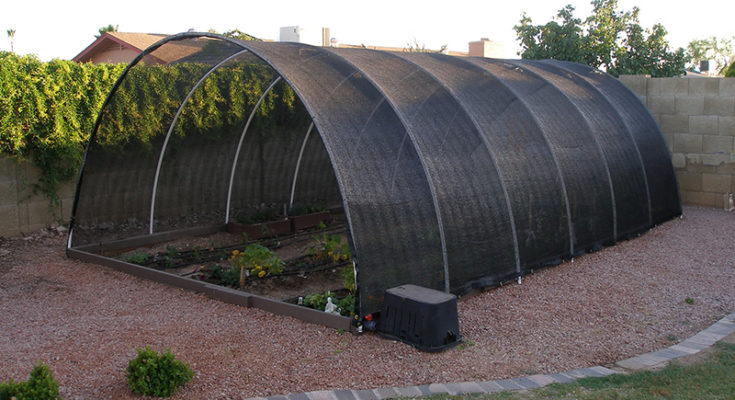 Shade cloth in black covers the large hoop greenhouse structure to protect plants from the sun.